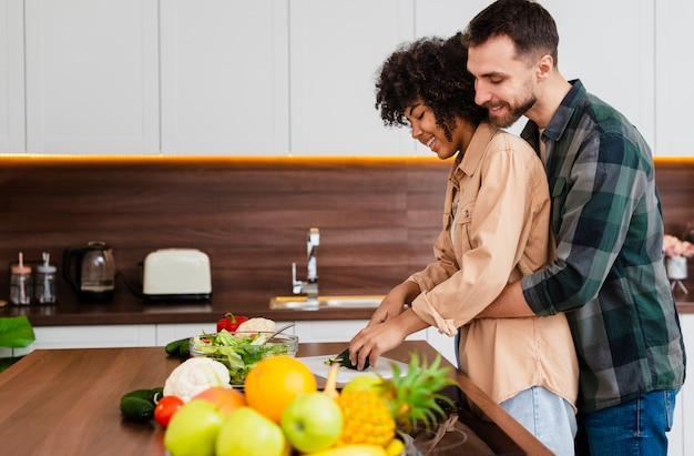 Vista lateral hombre abrazando mujer cocina