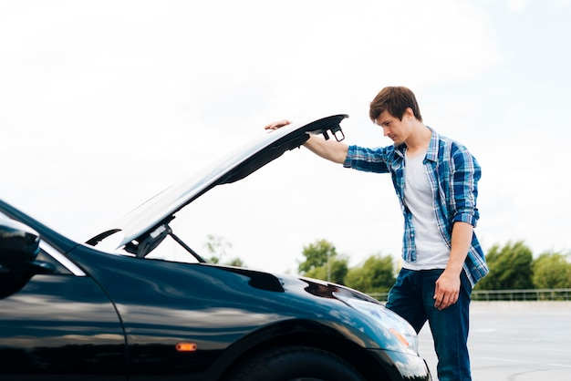 Vista lateral del hombre abriendo el capó del coche