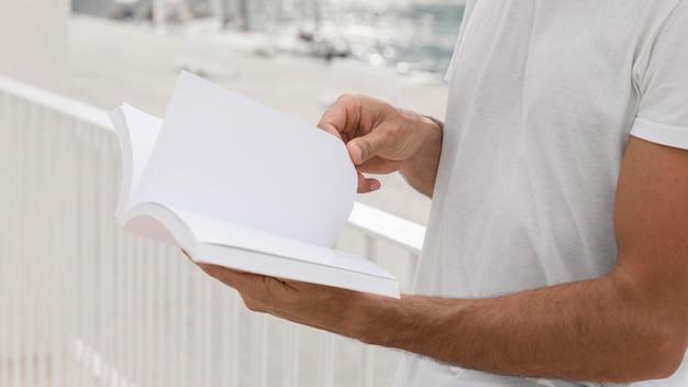 Vista lateral, de, hombre, aire libre, tenencia, libro