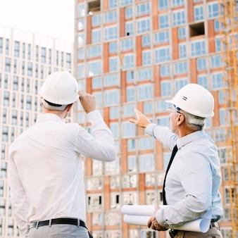 Vista lateral hombre apuntando al andamio del edificio