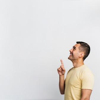 Vista lateral hombre apuntando hacia arriba con espacio de copia