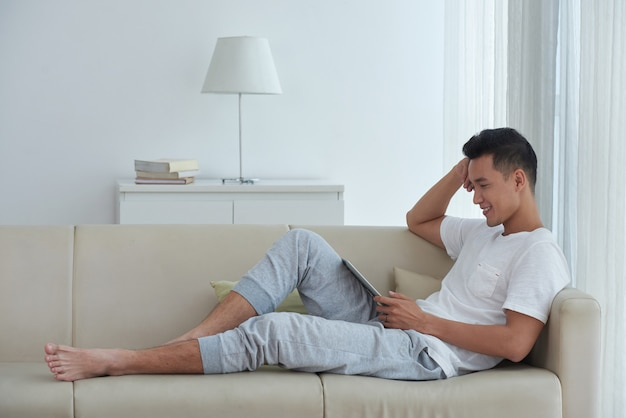 Vista lateral del hombre asiático sentado cómodamente en el sofá y viendo videos en su teclado digital