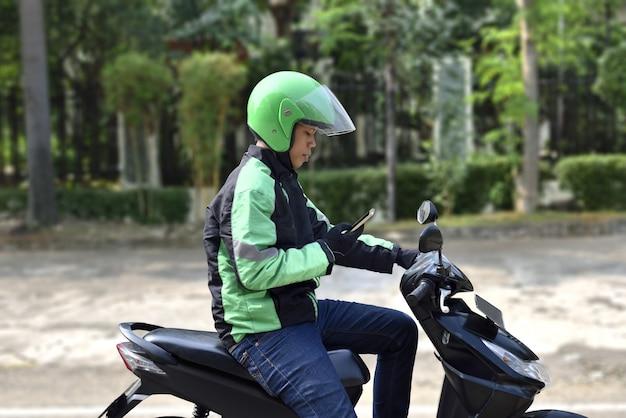 Vista lateral del hombre asiático del taxi de la motocicleta que comprueba el teléfono