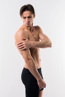 Vista lateral del hombre atlético posando sin camisa