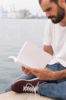 Vista lateral del hombre con barba leyendo un libro junto al lago