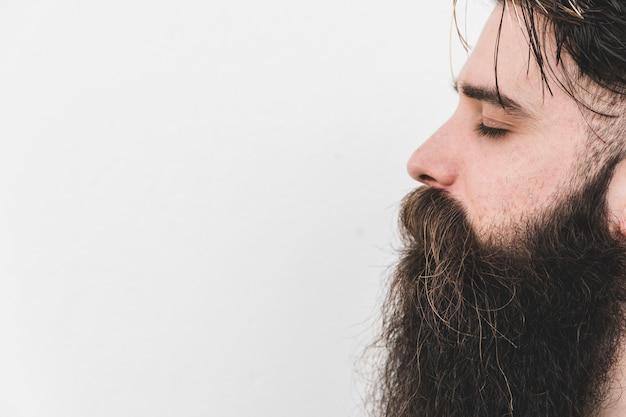 Vista lateral de un hombre barbudo largo que cierra su ojo contra el fondo blanco