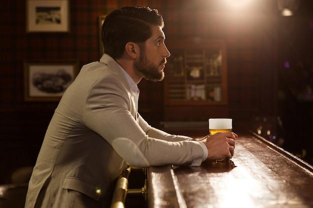 Vista lateral de un hombre barbudo sentado en el pub