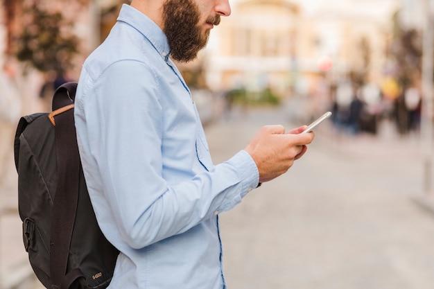 Vista lateral de un hombre barbudo usando teléfono celular