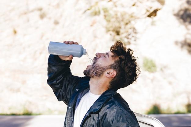Vista lateral del hombre con botella de agua