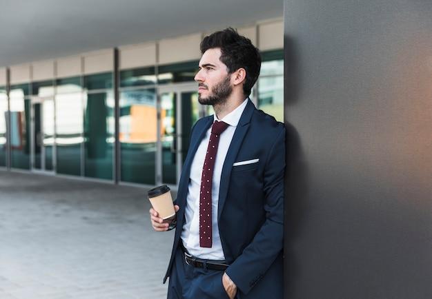 Vista lateral hombre con café mirando a otro lado
