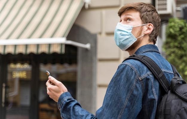 Vista lateral del hombre caminando afuera con una máscara médica en