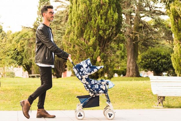 Vista lateral de un hombre caminando con un cochecito de bebé en el parque