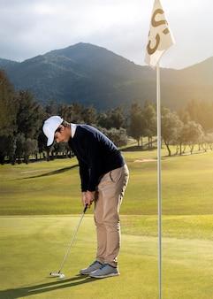 Vista lateral del hombre en el campo de golf con club y bandera