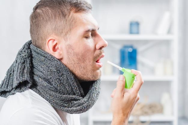 Vista lateral de un hombre chorros de garganta con spray.
