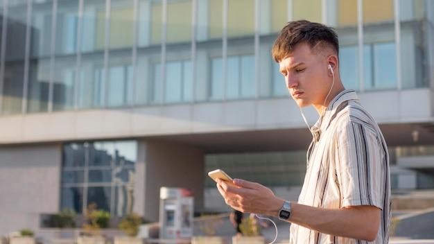 Vista lateral del hombre en la ciudad escuchando música con auriculares