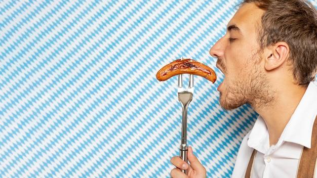 Vista lateral del hombre comiendo salchichas alemanas
