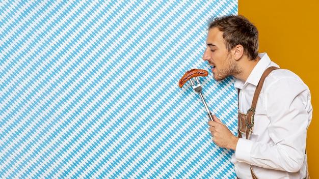 Vista lateral del hombre comiendo salchichas