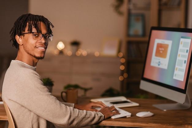 Vista lateral del hombre con computadora personal en casa