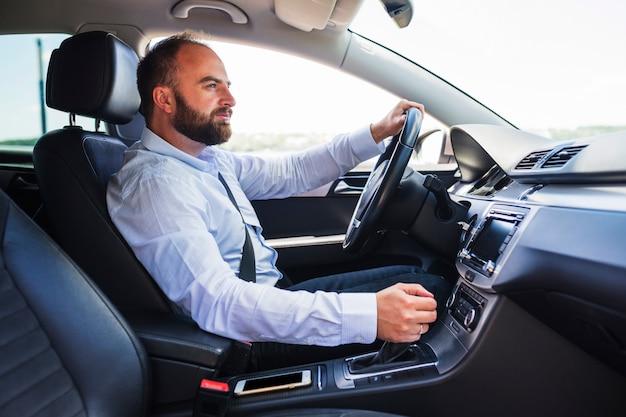 Vista lateral de un hombre conduciendo coche