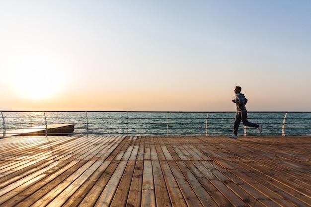 Vista lateral del hombre deportivo, corriendo en el muelle, cerca del mar