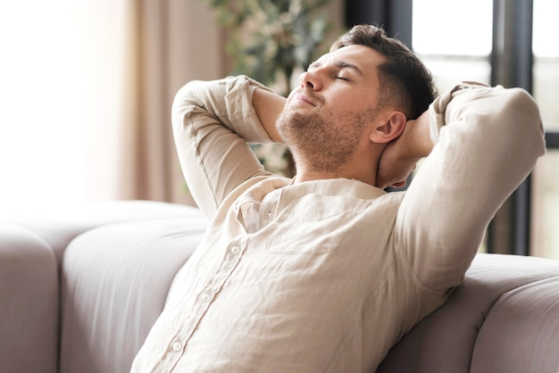 Vista lateral hombre descansando en el sofá