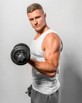 Vista lateral del hombre en forma con camiseta sin mangas sosteniendo pesas