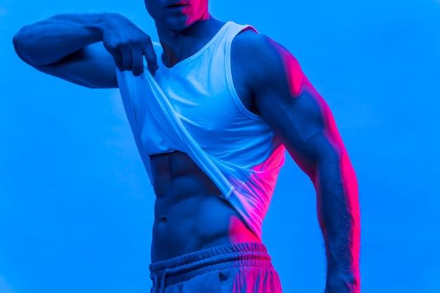 Vista lateral del hombre en forma posando mientras levanta la camiseta sin mangas