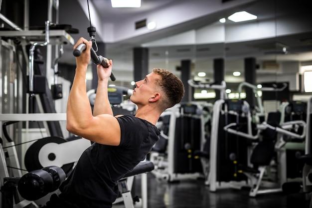 Vista lateral del hombre en el gimnasio levantando pesas
