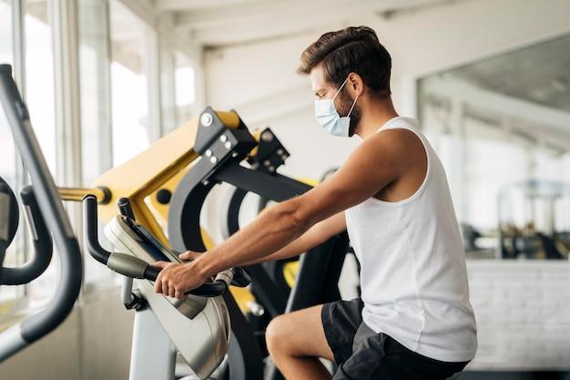 Vista lateral del hombre en el gimnasio trabajando con máscara médica