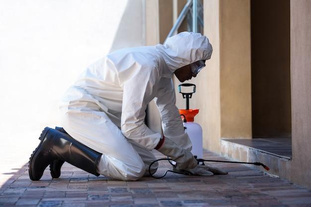 Vista lateral de un hombre haciendo control de plagas