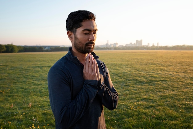 Vista lateral del hombre haciendo yoga al aire libre