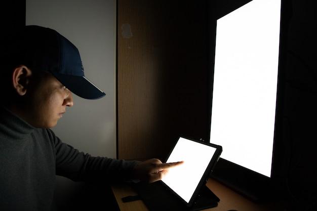 Vista lateral del hombre hacker sentado en el monitor de la computadora, tableta de pantalla blanca que señala los dedos
