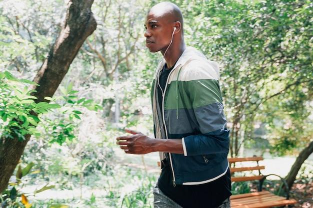 Vista lateral de un hombre joven con el auricular en su oreja corriendo en el parque