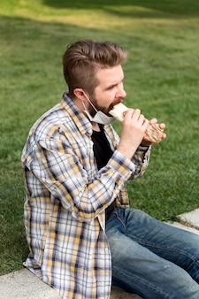 Vista lateral del hombre joven comiendo comida rápida