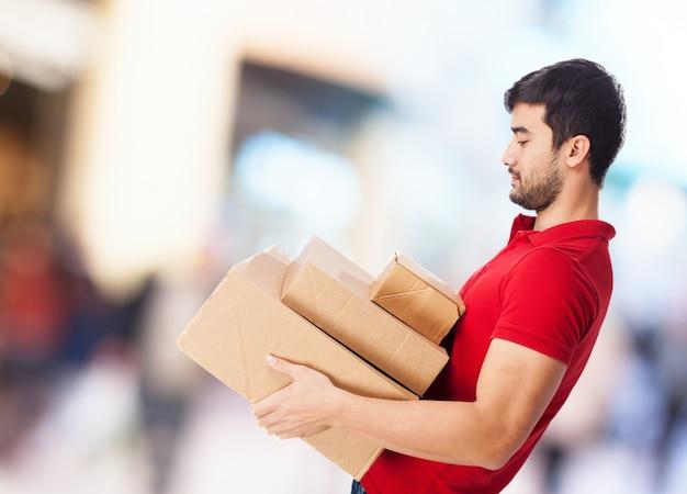 Vista lateral de hombre joven llevando unas cajas