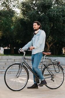 Vista lateral de un hombre joven de pie con bicicleta en el parque