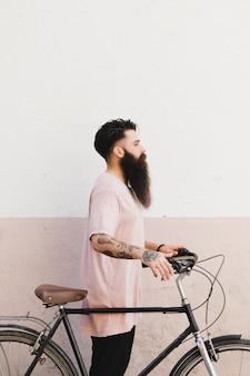 Vista lateral de un hombre joven de pie con su bicicleta contra la pared