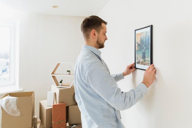 Vista lateral de un hombre joven que fija el marco de imagen en la pared en el nuevo hogar