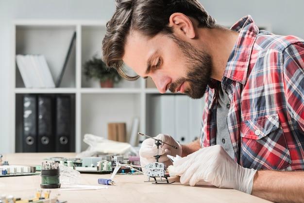 Vista lateral de un hombre joven que repara el juguete del helicóptero sobre el escritorio de madera