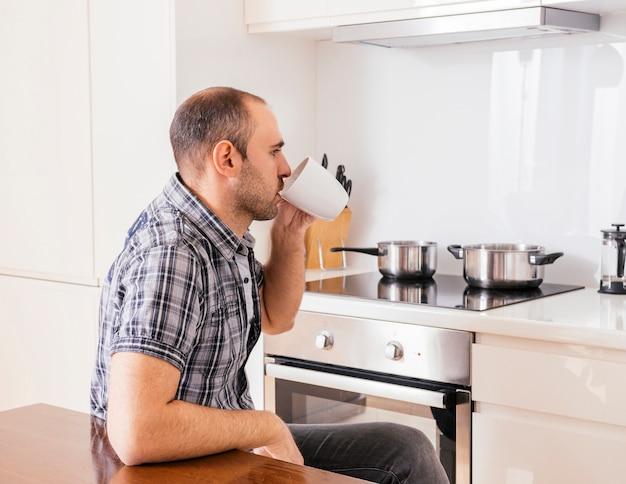 Vista lateral de un hombre joven sentado en la cocina tomando el café.