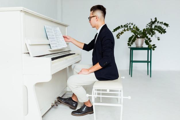 Vista lateral de un hombre joven sentado frente al piano leyendo la hoja musical