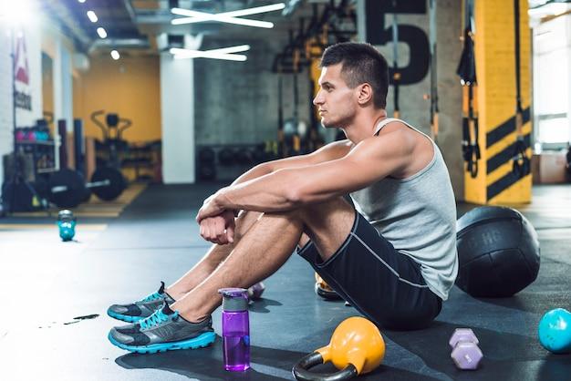 Vista lateral de un hombre joven sentado en el piso cerca de equipos de ejercicios y una botella de agua