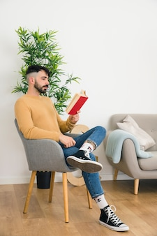 Vista lateral del hombre joven serio hermoso que se sienta en la silla que lee el libro