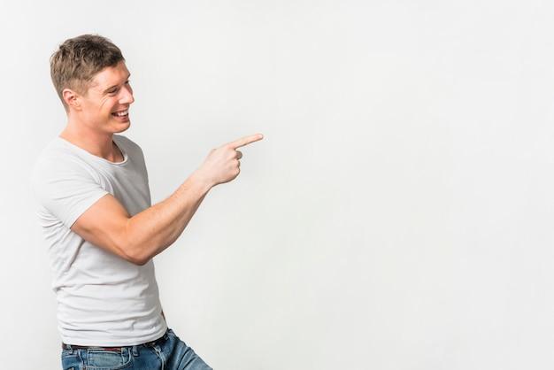 Vista lateral de un hombre joven sonriente que señala su dedo en algo contra el fondo blanco