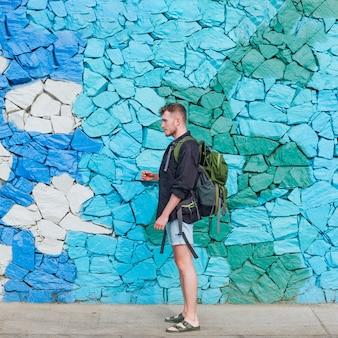 Vista lateral del hombre joven viajero con mochila contra el muro de piedra