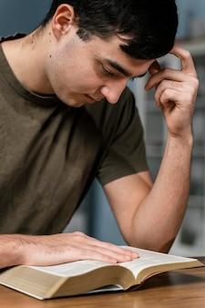 Vista lateral del hombre leyendo la biblia