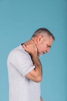Vista lateral de un hombre maduro que sufre de dolor de cuello.