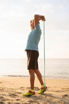Vista lateral del hombre maduro trabajando con cuerda elástica en la playa
