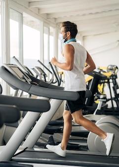 Vista lateral del hombre con máscara médica en la cinta en el gimnasio