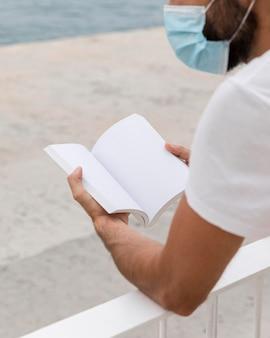 Vista lateral del hombre con máscara médica junto al lago con libro